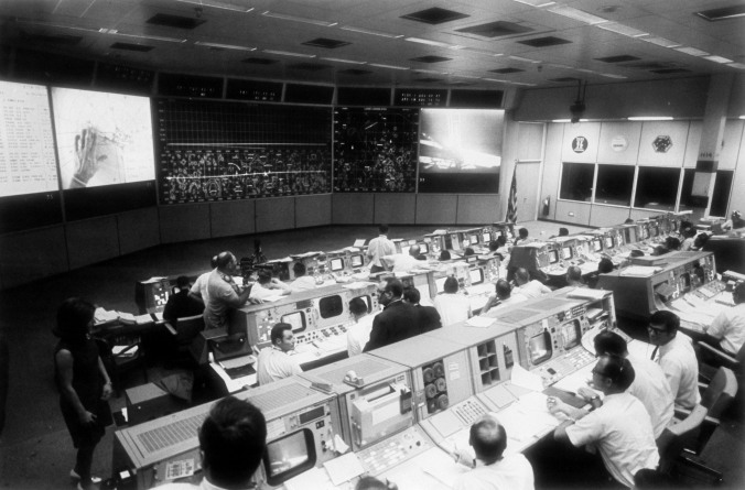 Overall view of Mission Control Center with dozens of people sitting at computer terminals